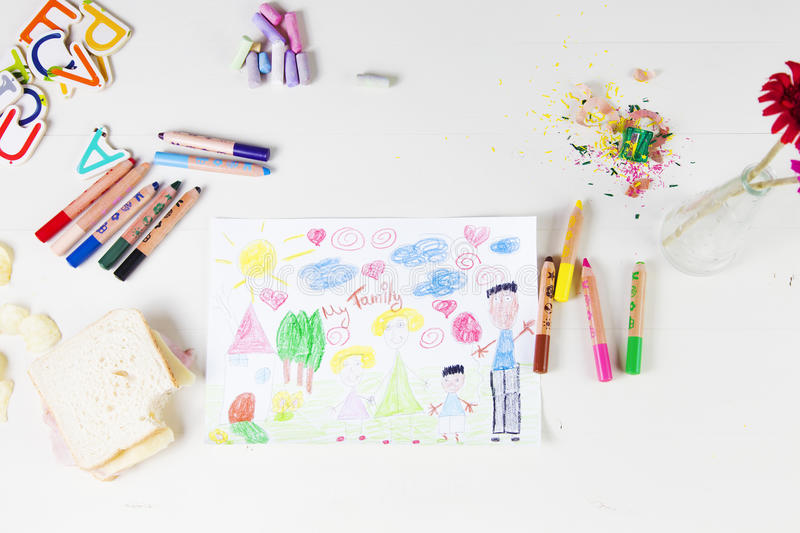 Kids drawing of multi-racial Family and colored pencils on wooden table royalty free stock image