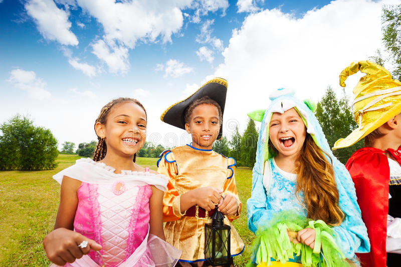Kids dressed wearing Halloween costumes in park stock images