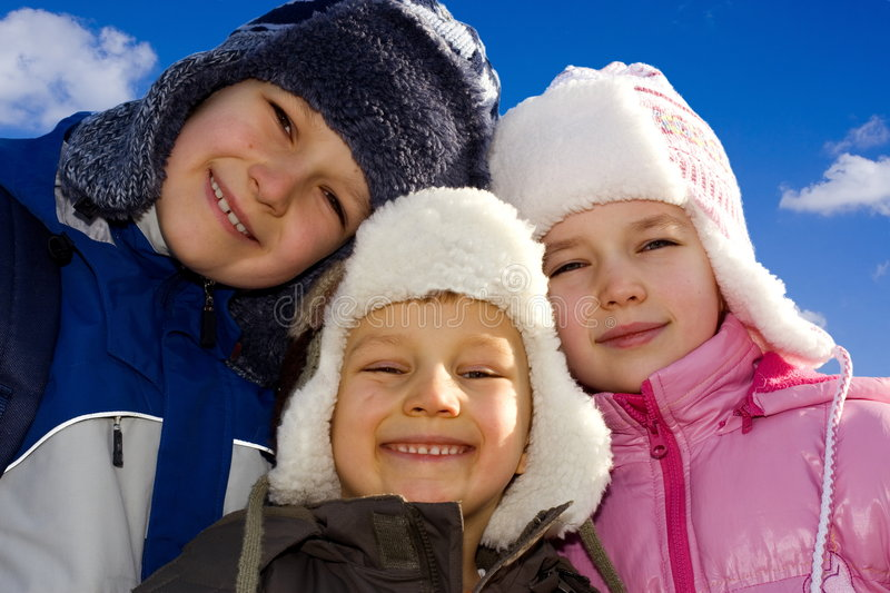Kids Dressed for Winter-3. Three smiling, happy brothers and sisters, all dressed in warm winter coats and hats, eagerly have their picture taken outdoors on a royalty free stock photo