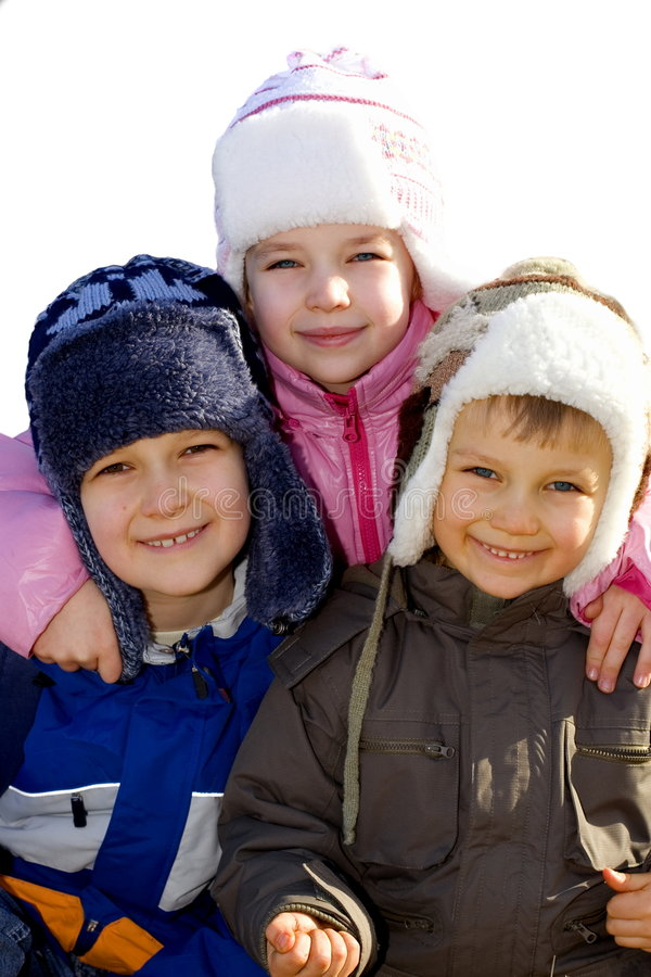 Kids Dressed for Winter-4. Two smiling and happy brothers and a sister dressed in warm hats and coats, eagerly pose for a picture outside on a cold winter day stock photos