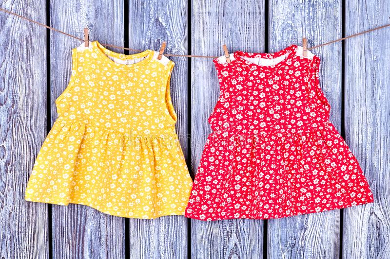 Kids dresses hanging on rope. Baby-girl apparel drying on clothesline, old wooden background royalty free stock image