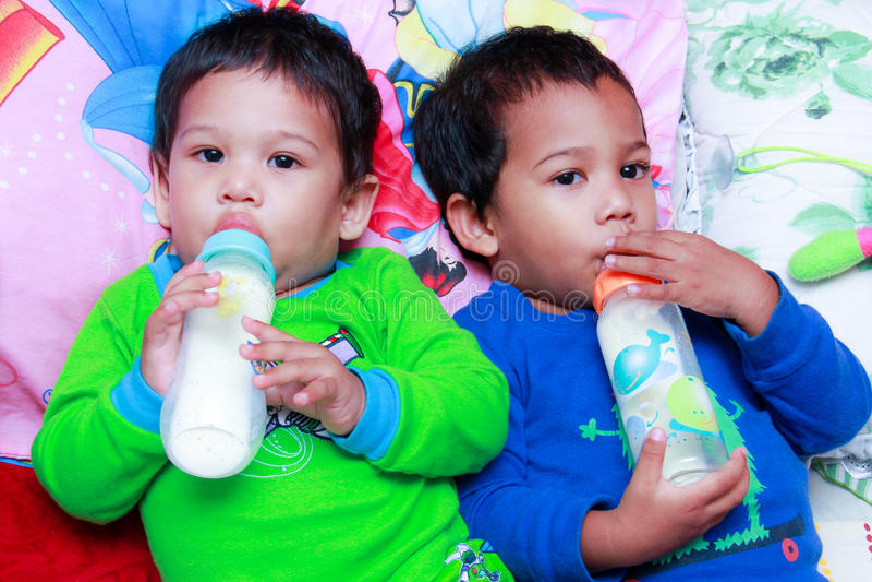 Kids drink bottled formula milk stock images