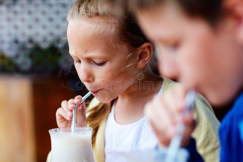Kids drinking milkshakes. Kids brother and sister drinking milkshakes in outdoor cafe stock images