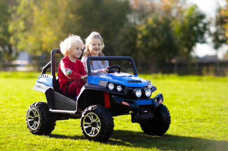Kids driving electric toy car. Outdoor toys stock image