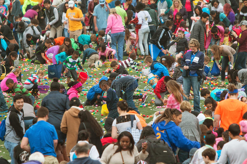 Kids Eagerly Participate In Massive Community Easter Egg Hunt. Marietta, GA, USA - March 26, 2016: Kids and parents eagerly grab plastic eggs and candy at the stock photos
