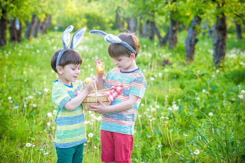 Kids on Easter egg hunt in blooming spring garden. Children searching for colorful eggs in flower meadow. Toddler boy and his brot. Her friend kid boy play stock photos