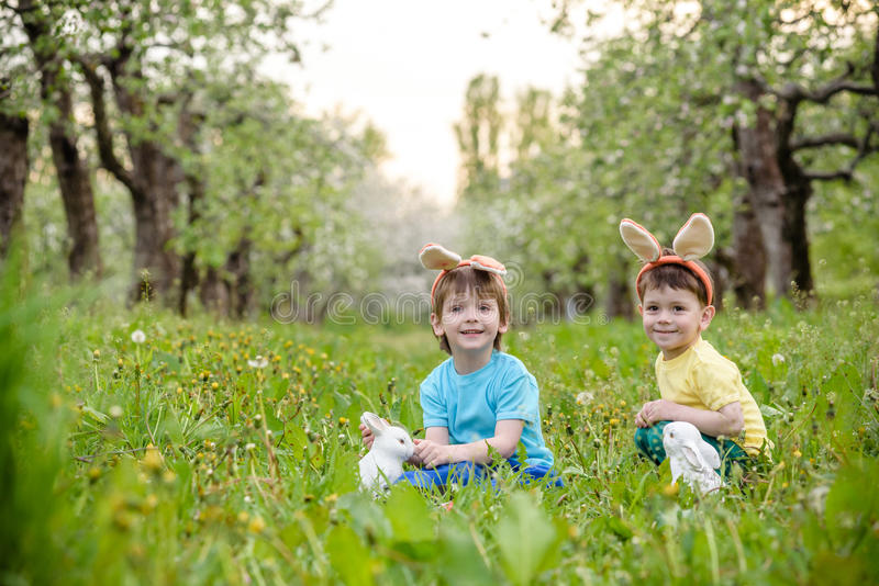Kids on Easter egg hunt in blooming spring garden. Children searching for colorful eggs in flower meadow. Toddler boy and his brot. Her friend kid boy play stock images