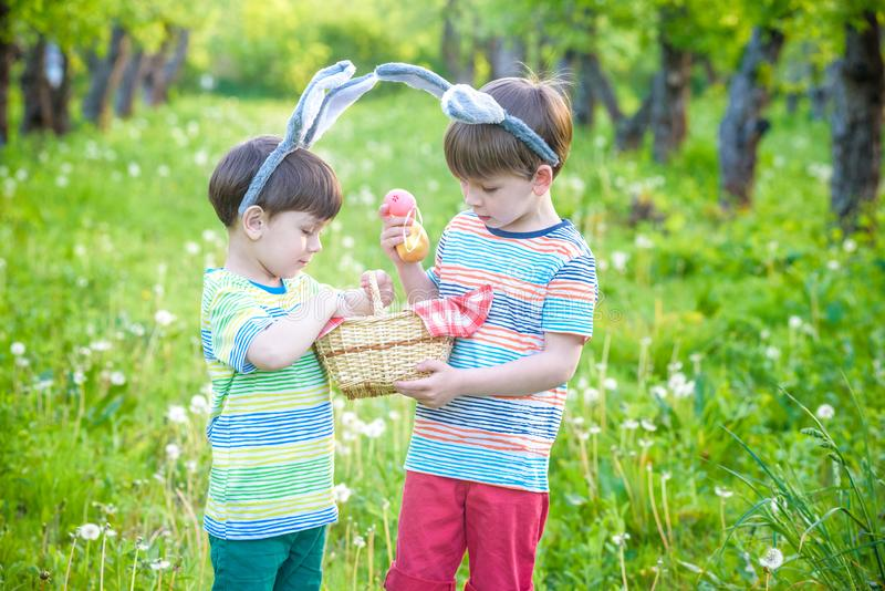 Kids on Easter egg hunt in blooming spring garden. Children searching for colorful eggs in flower meadow. Toddler boy and his brot. Her friend kid boy play stock photography