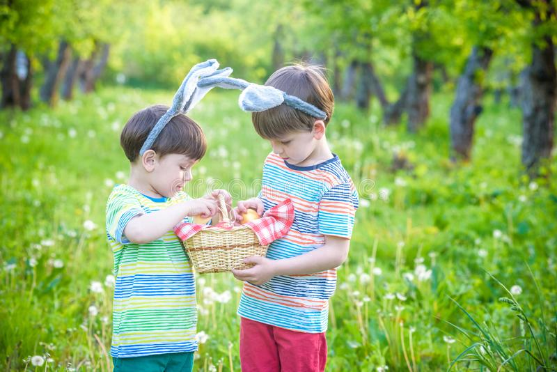 Kids on Easter egg hunt in blooming spring garden. Children searching for colorful eggs in flower meadow. Toddler boy and his. Brother friend kid boy play royalty free stock photos