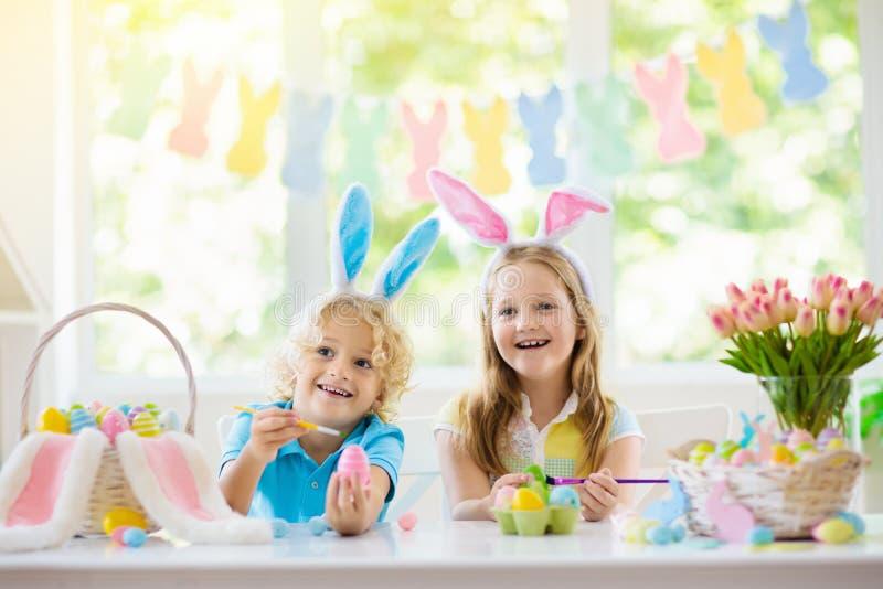 Kids on Easter egg hunt. Children dye eggs. Kids dyeing Easter eggs. Children in bunny ears dye colorful egg for Easter hunt. Home decoration with flowers royalty free stock images