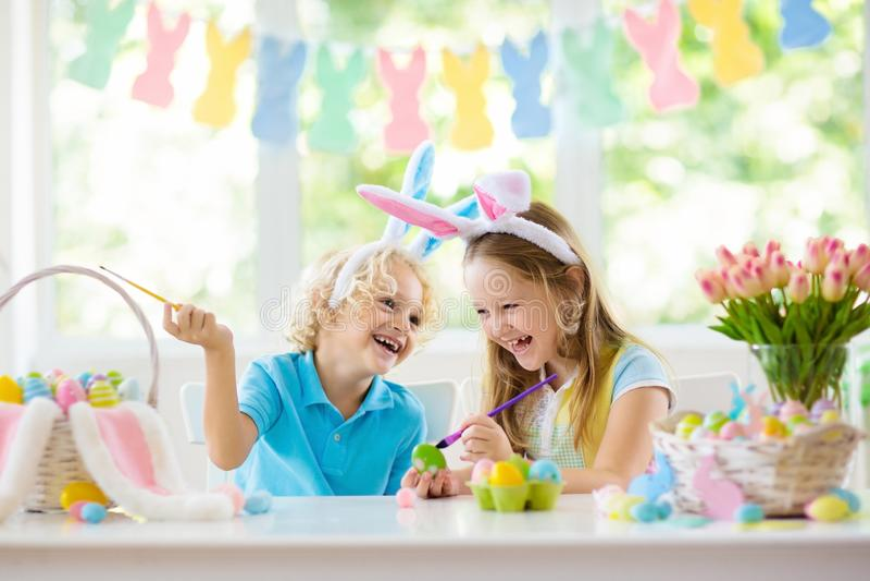 Kids on Easter egg hunt. Children dye eggs. Kids dyeing Easter eggs. Children in bunny ears dye colorful egg for Easter hunt. Home decoration with flowers royalty free stock photos