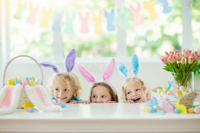 Kids on Easter egg hunt. Children dye eggs. Kids dyeing Easter eggs. Children in bunny ears dye colorful egg for Easter hunt. Home decoration with flowers stock photography