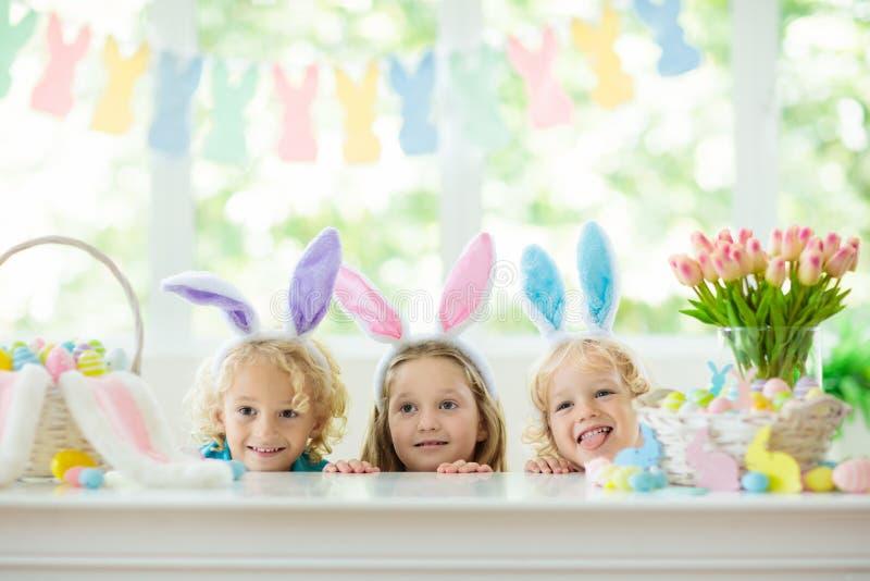 Kids on Easter egg hunt. Children dye eggs. Kids dyeing Easter eggs. Children in bunny ears dye colorful egg for Easter hunt. Home decoration with flowers stock photos