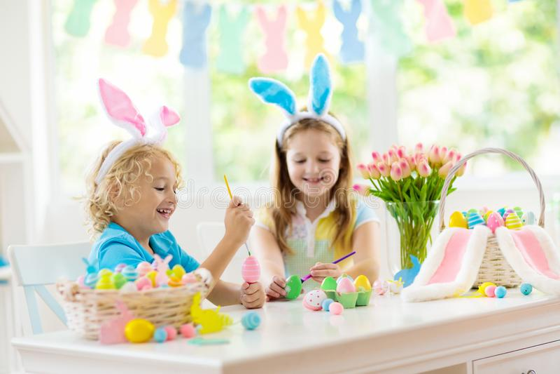 Kids on Easter egg hunt. Children dye eggs. Kids dyeing Easter eggs. Children in bunny ears dye colorful egg for Easter hunt. Home decoration with flowers stock images