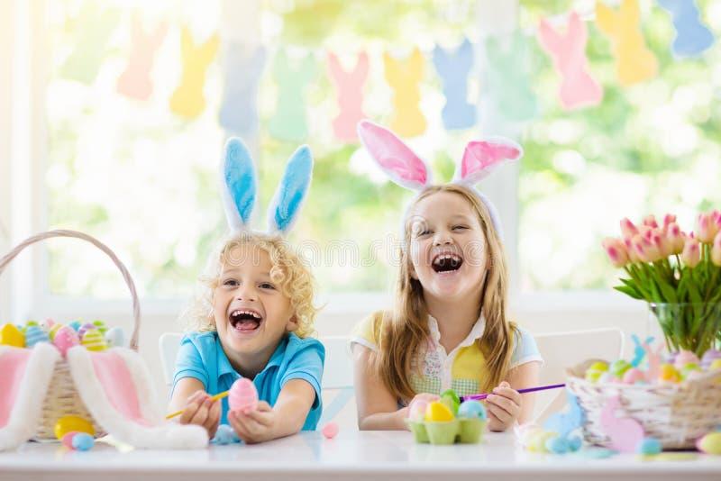 Kids on Easter egg hunt. Children dye eggs. Kids dyeing Easter eggs. Children in bunny ears dye colorful egg for Easter hunt. Home decoration with flowers royalty free stock photography