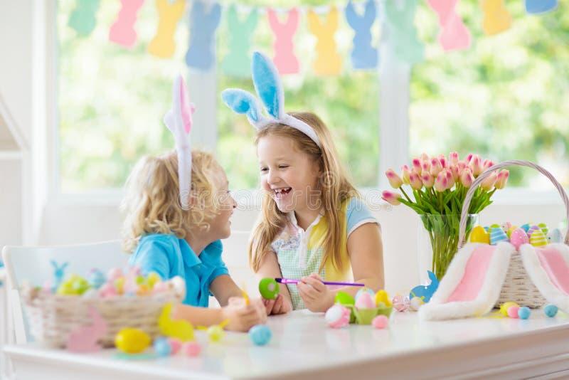 Kids on Easter egg hunt. Children dye eggs. Kids dyeing Easter eggs. Children in bunny ears dye colorful egg for Easter hunt. Home decoration with flowers royalty free stock photo