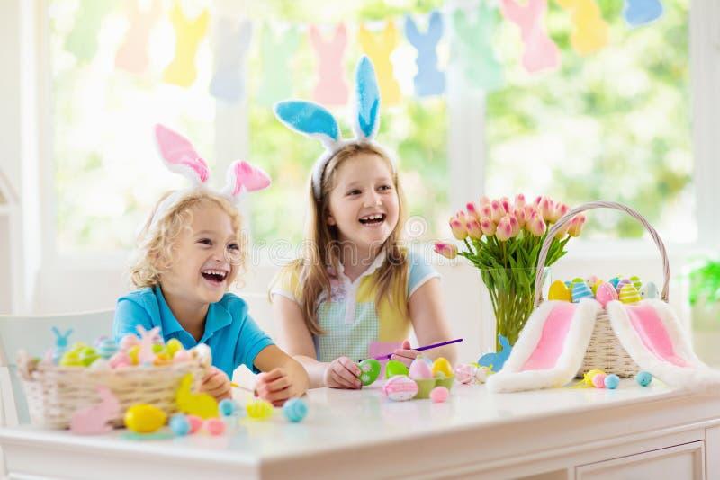 Kids on Easter egg hunt. Children dye eggs. Kids dyeing Easter eggs. Children in bunny ears dye colorful egg for Easter hunt. Home decoration with flowers stock image