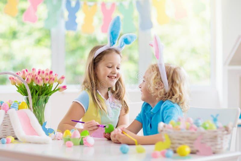 Kids on Easter egg hunt. Children dye eggs. Kids dyeing Easter eggs. Children in bunny ears dye colorful egg for Easter hunt. Home decoration with flowers stock photo