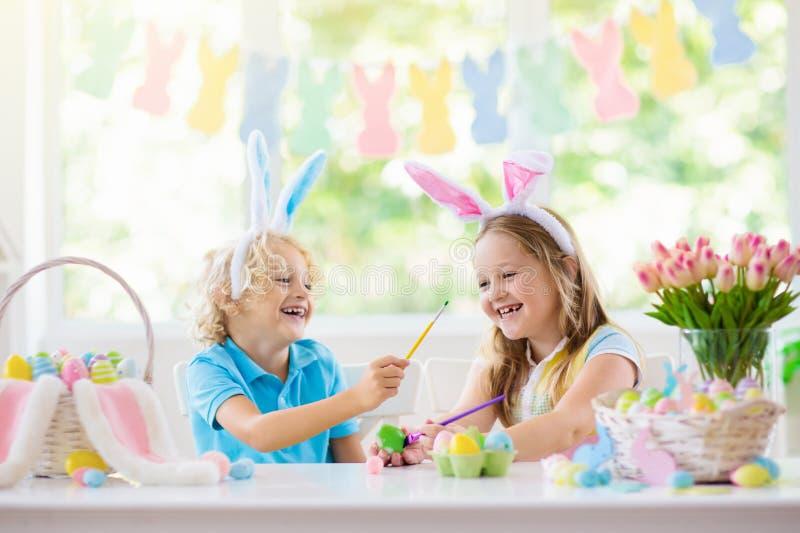 Kids on Easter egg hunt. Children dye eggs. Kids dyeing Easter eggs. Children in bunny ears dye colorful egg for Easter hunt. Home decoration with flowers royalty free stock image