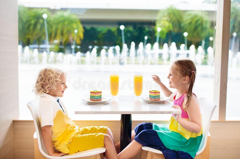 Kids eat cake at restaurant. Boy and girl in cafe. stock photo