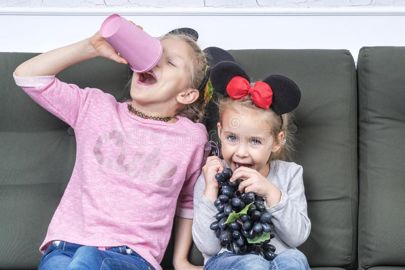 Kids eat on the couch. Two little beautiful girls play sitting on the couch, pretend to drink from pink glass and eat artificial grapes royalty free stock images