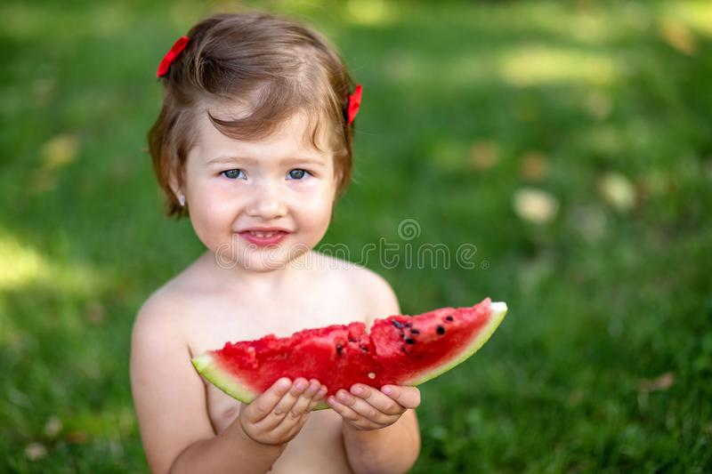 Kids eat fruit outdoors. Healthy snack for children. Little girl playing in the garden holding a slice of water melon. royalty free stock image