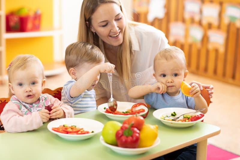 Kids eat in nursery royalty free stock photo
