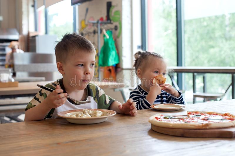 Kids eat pizza and meat dumplings at cafe. children eating unhealthy food indoors. Siblings in the cafe, family holiday concept royalty free stock image