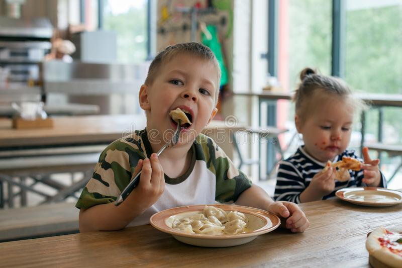 Kids eat pizza and meat dumplings at cafe. children eating unhealthy food indoors. Siblings in the cafe, family holiday concept.  royalty free stock photos