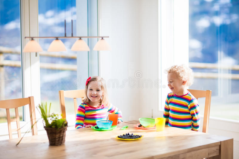 Kids eating breakfast at home. Fruit and milk for children. Children enjoying breakfast in sunny kitchen with big windows. Kids eating fruit cereal and berry stock image