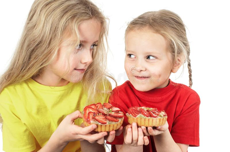 Kids eating fruit cakes. Two happy little girls eating fruit cakes royalty free stock photos