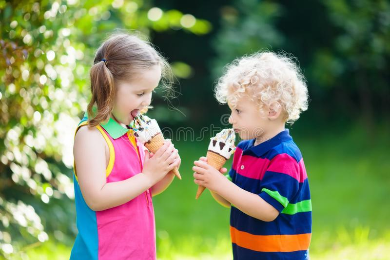 Kids eating ice cream. Child with fruit dessert. Kids eating ice cream on hot summer day on tropical vacation. Children eat frozen yoghurt. Boy and girl with royalty free stock image