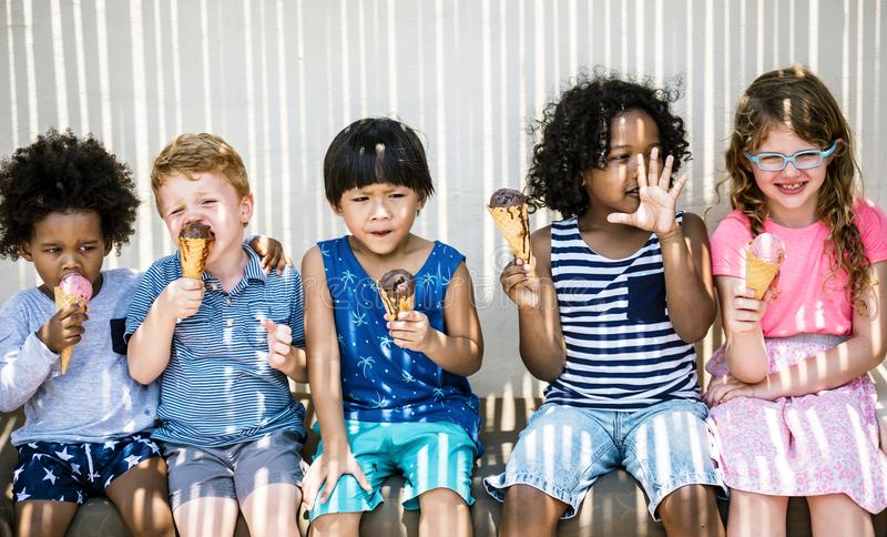 Kids eating ice cream in the summer stock photo