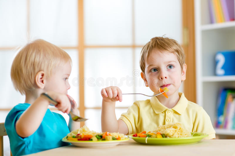 Kids eating in kindergarten or at home stock photos