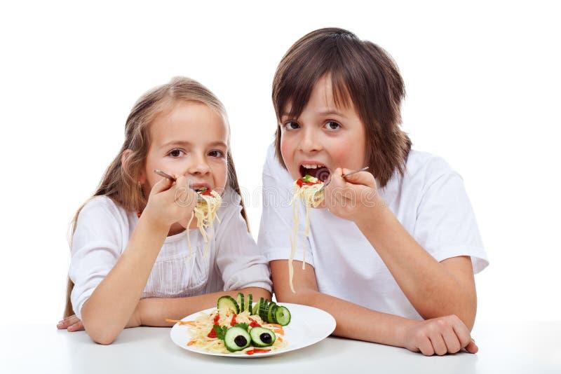 Kids eating a pasta dish royalty free stock photos