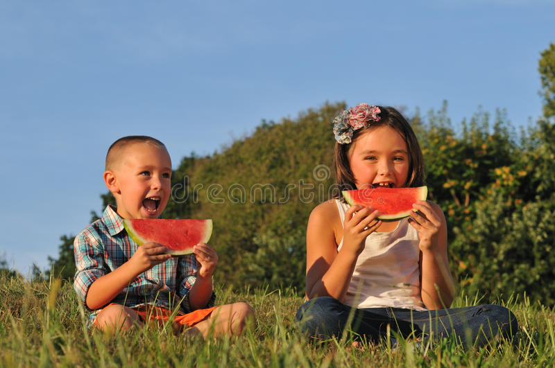 Kids eating sliced Watermelon royalty free stock photos