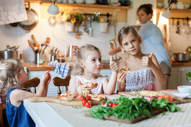 Kids are eating and tasting italian homemade pizza with mother. royalty free stock photography