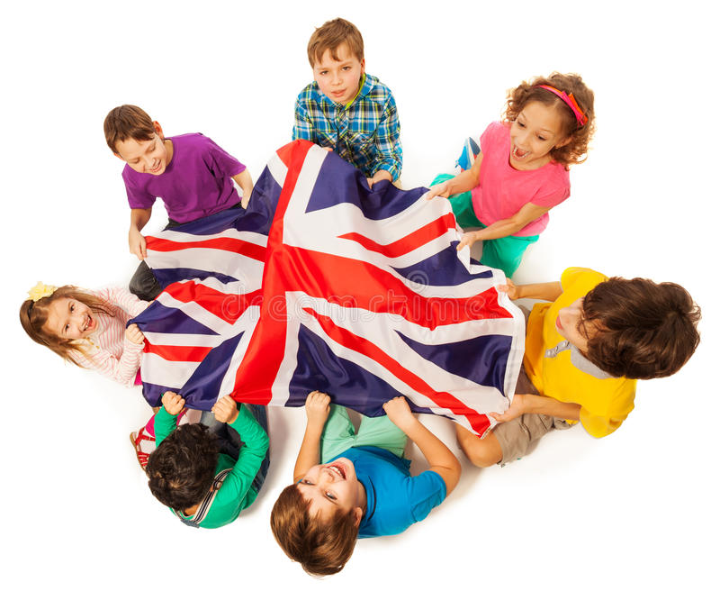Kids with English flag in a middle of their circle. Top view of seven kids holding English flag in the middle of their circle, isolated on white background royalty free stock photography