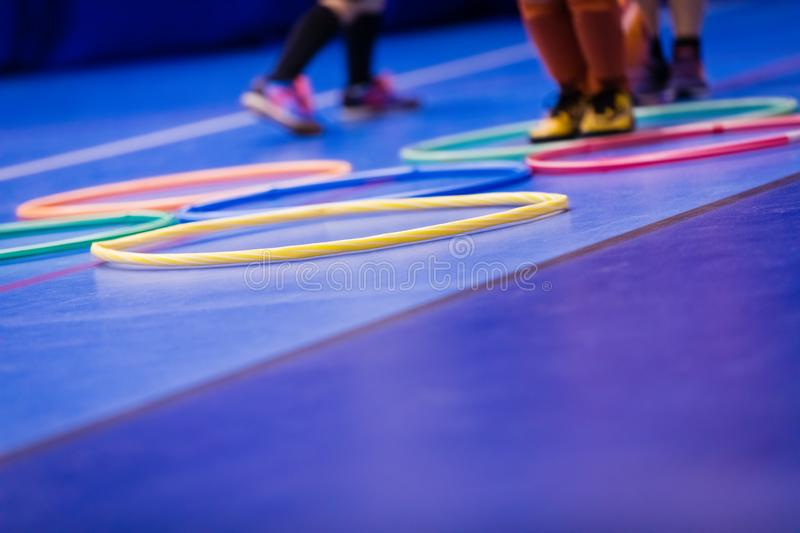Kids Enjoying Physical Education Class. Gym Class for Children. Kids Jumping Using Hula-Hoop royalty free stock photo