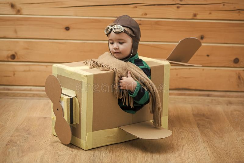 Kids enyoj happy day. Brave dreamer boy playing with a cardboard airplane stock photography