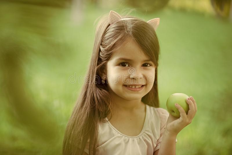 Kids enyoj happy day. Child smile with green apple fruit on nature, food royalty free stock photography