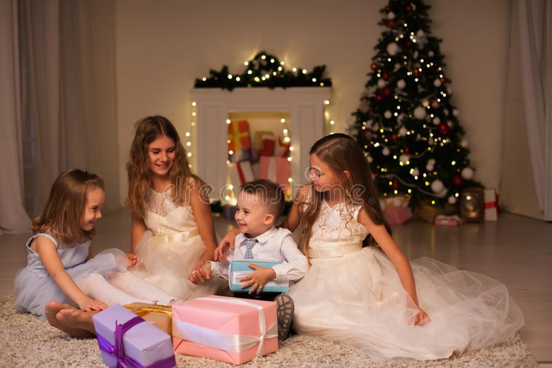 Kids family open gifts at New Year`s Christmas Tree royalty free stock photos