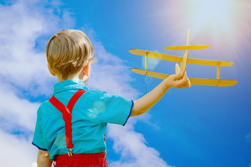Kids fantasy. Child playing with toy airplane against sky and cl. Ouds background. Care of childrens dreams royalty free stock image