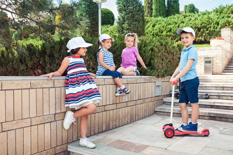 Kids fashion Concept. The group of teen boys and girls posing ar park. Children colorful clothes, lifestyle, trendy colors concepts. Caucasian models - boys stock images