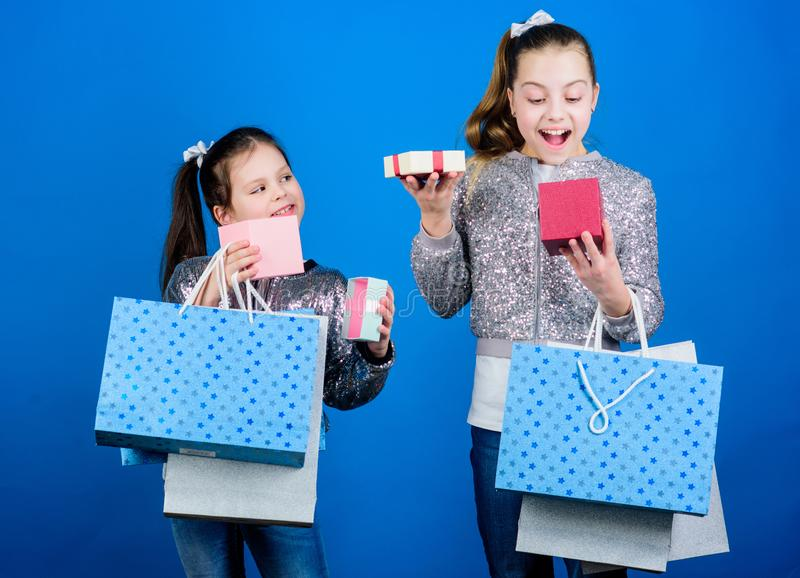 Kids fashion. Girls sisters friends with shopping bags blue background. Every product delivered to you. Shopping and. Purchase. Black friday. Sale and discount stock photography