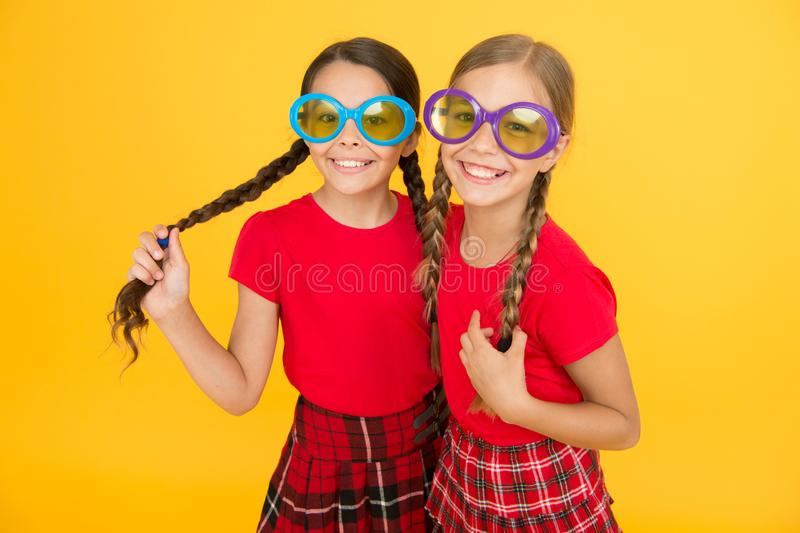 Kids fashionable friends posing in sunglasses on yellow background. Summer fashion trend. Summer fun. Summer accessory. Girls cute sisters similar outfits wear royalty free stock images