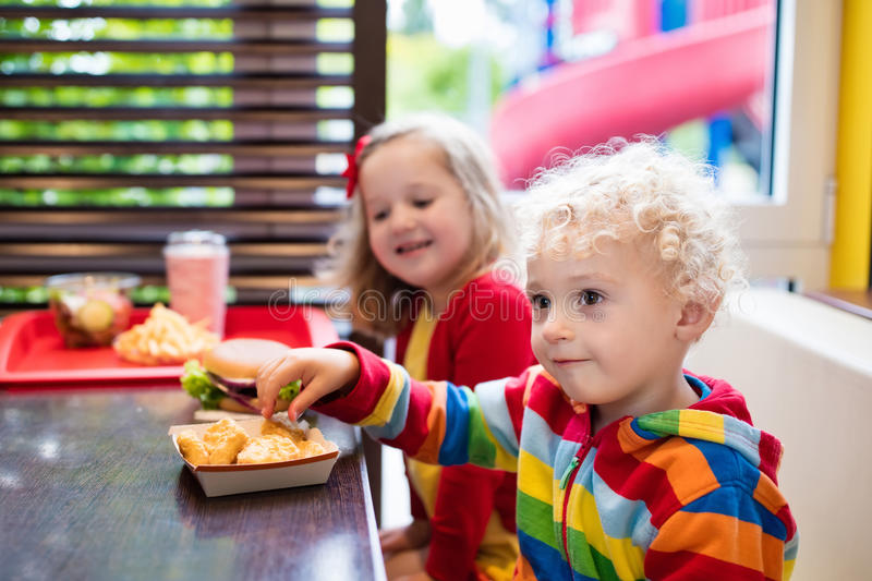 Kids in a fast food restaurant. Little girl and boy eating chicken nuggets, hamburger and French fries in a fast food restaurant. Child with sandwich and potato royalty free stock image