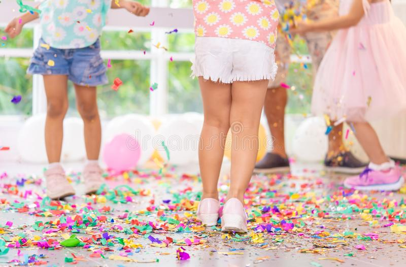 Kids feet run in colorful paper party floor. Kids feet running in colorful paper party floor stock image