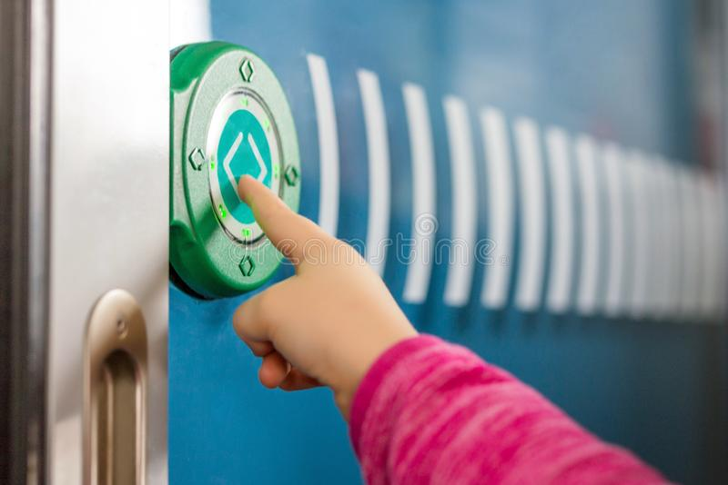 Kids finger pushing green round touch button with arrows. Transparent door between carriages in intercity train. Modern sensot stock photos