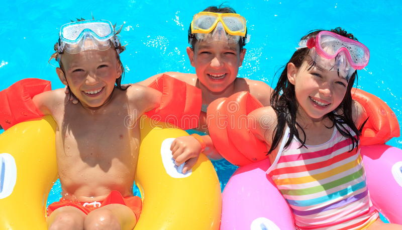 Kids floating in swimming pool. Happy, smiling kids on inflatable floats in a swimming pool royalty free stock photo